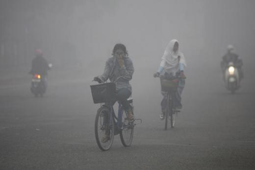 Siswa naik sepeda di tengah kepungan asap di Kota Sampit, Kalimantan Tengah. September 28, 2012. REUTERS/Sigit Pamungkas