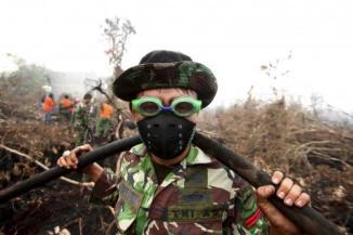 Seorang tentara mengenakan kacamata untuk melindungi mata dari pedihnya polusi asap. ketika memadamkan api di desa Parit Indah Village, Kampar, Riau, 8 September 2015. REUTERS/YT Haryono