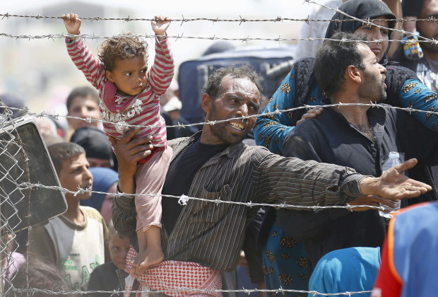 A Syrian refugee reacts as he waits behind border fences to cross into Turkey at Akcakale border gate in Sanliurfa province, Turkey, June 15, 2015. On Sunday, Turkish authorities reopened the border after a few days of closure, a security source said, adding that they expected as many as 10,000 people to come across. REUTERS/Umit Bektas TPX IMAGES OF THE DAY      - RTX1GJZC