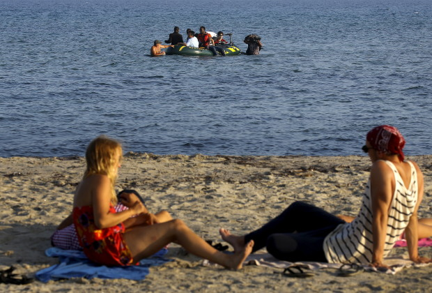 Tourists lie on a beach as migrants and refugees from Syria and Africa arrive on a dinghy at the Greek island of Kos after crossing a part of the Aegean Sea between Turkey and Greece, August 8, 2015.   The U.N refugee agency, UNHCR, estimates that Greece has received more than 107,000 refugees and migrants this year, more than double its 43,500 intake of 2014. REUTERS/ Yannis Behrakis  - RTX1NK0A