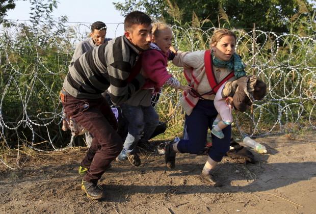 Pengungsi menjebol pagar perbtasan Serbia -Hongaria.  27 Agustus 2015. Pemerintah Hongaria menerjunkan ratusan polisi dan tentara dilengkapi dengan kendaraan militer dan helikopter untuk menghalau pengungsi. REUTERS/Bernadett Szabo