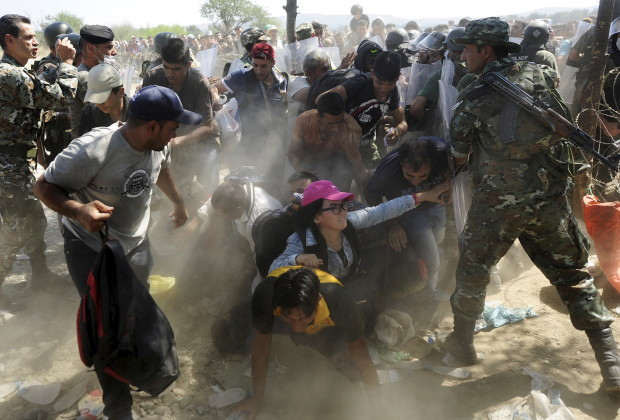 Migrants fall as they rush to cross into Macedonia after Macedonian police allowed a small group of people to pass through a passageway, as they try to regulate the flow of migrants at the Macedonian-Greek border September 2, 2015. Up to 3,000 migrants are expected to cross into Macedonia every day in the coming months, most of them refugees fleeing war, particularly from Syria, the United Nations said last week.   REUTERS/Ognen Teofilovski - RTX1QR46