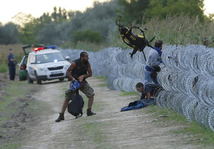 Hungarian police positioned nearby watch as Syrian migrants climb under a fence to enter Hungary at the Hungarian-Serbian border near Roszke