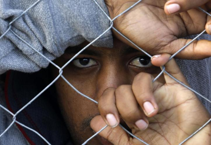 A stranded Bangladeshi migrant looks through a police fence during a protest at the Greek-Macedonian border near the Greek village of Idomeni