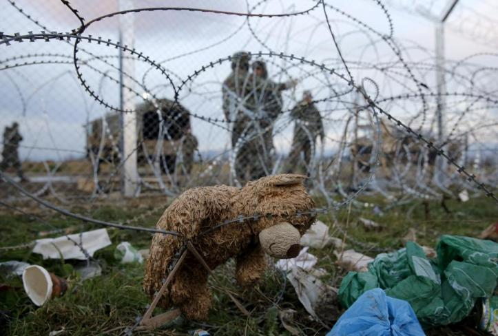 A teddy bear is seen on barbed wire in front of Macedonian police at the Greek-Macedonian border