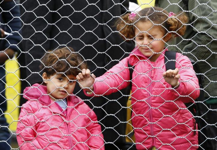 Migrants' children wait to cross the border from Slovenia into Spielfeld in Austria