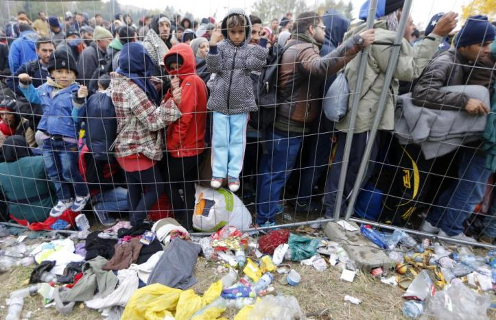 Children climb on a fence as migrants queue to cross the border into Spielfeld in Austria from the village of Sentilj