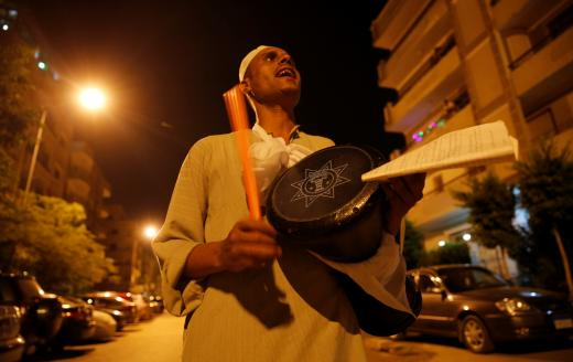 El Mesaharty, Hussien, 40, wakes up residents for their pre-dawn meals during the first day of Ramadan in Cairo