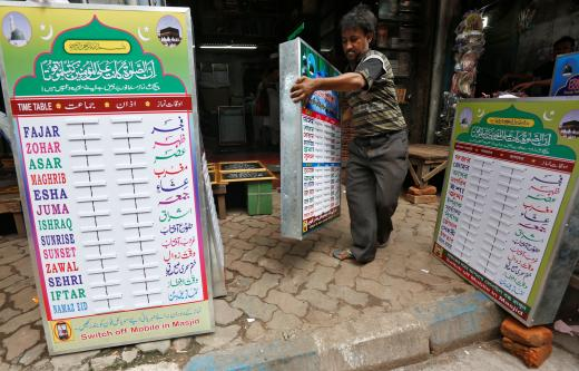 A salesman carries a prayer timetable to display it for sale ahead of the Muslim fasting month of Ramadan in Kolkata