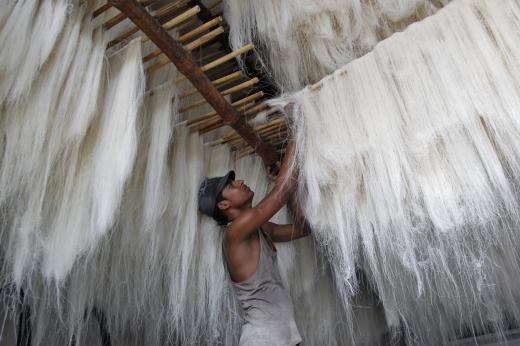 A worker hangs strands of vermicelli, a specialty eaten during the Muslim holy fasting month of Ramadan, to dry at a factory in Allahabad