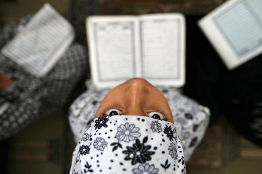 Palestinian girl reads the Koran during the holy fasting month of Ramadan at a mosque in Rafah in the southern Gaza Strip